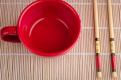 Chopsticks and red cup Stock Photos
