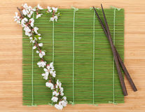 Chopsticks and sakura branch over bamboo mat Stock Photography
