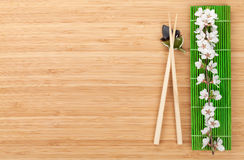 Chopsticks and sakura branch over bamboo mat Stock Images