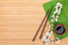 Chopsticks, sakura branch, soy sauce and bamboo mat Royalty Free Stock Image