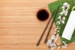 Chopsticks, sakura branch, soy sauce and bamboo mat Royalty Free Stock Photos