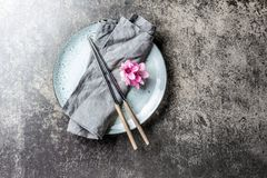 Chopsticks and sakura flowers on gray plate, stone background. Japanese food concept. Top view, copy space. Stock Photo