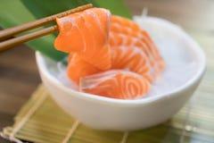 Chopsticks with Salmon sashimi with Salmon sashimi on ice in with bowl. japanese food in Asian restuarant.  stock image