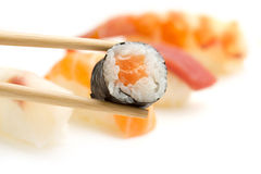 Chopsticks with salmon sushi roll Royalty Free Stock Image