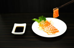 Chopsticks with sliced raw salmon lisolated Royalty Free Stock Image