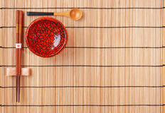 Chopsticks, spoon and red bowl on bamboo Royalty Free Stock Images