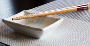 Chopsticks sushi with cup. For soy sauce Royalty Free Stock Photo
