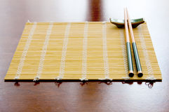 Chopsticks on table mat. Chopsticks with rests on table mat royalty free stock images