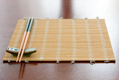 Chopsticks on table mat. Chopsticks with rests on table mat stock images