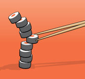 Chopsticks taking a middle roll of a sushi tower Royalty Free Stock Image