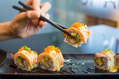 Chopsticks taking a section of sushi rolls, delicious sushi on a. Black plate on the dining table.Soft focus stock photos