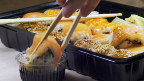 Chopsticks Taking Sushi Roll and Dip into Soy Sauce. stock footage