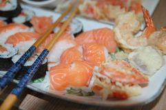 Chopsticks on Top of Variety of Sushi on Plate Stock Photo