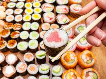 Chopsticks with tuna nori roll over lot of sushi. Fingers hold chopsticks with tuna nori roll over lot of sushi and rolls on wooden table royalty free stock images
