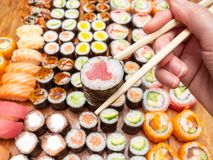 Chopsticks with tuna roll over assortment of sushi. Fingers hold chopsticks with tuna nori roll over assortment of sushi and rolls on wooden table stock photography