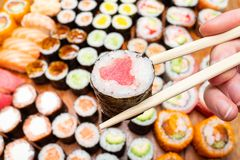 Chopsticks with tuna roll over set of sushi. Fingers hold chopsticks with tuna nori roll over set of sushi and rolls on wooden table stock image