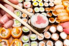 Chopsticks with tuna roll over various of sushi. Fingers hold chopsticks with tuna nori roll over various of sushi and rolls on wooden table stock photos