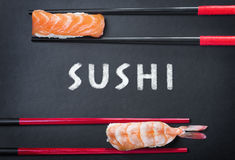 Chopsticks and two sushi and an inscription on a black backgroun Royalty Free Stock Images