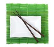 Chopsticks and utensils over bamboo mat Stock Photo