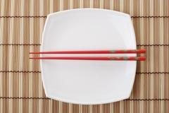Chopsticks vermelhos e prato branco em um guardanapo de bambu imagem de stock royalty free