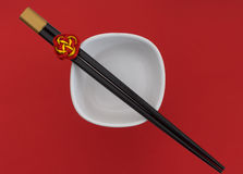 Chopsticks and white bowl on red Stock Photos