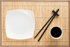 Chopsticks, white plate and bowl with soy sauce Royalty Free Stock Photo