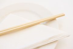 Chopsticks on white plate with paper napkin Stock Photography