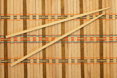 Chopsticks. On a wicker mat royalty free stock photo