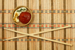 Chopsticks. On a wicker mat stock images