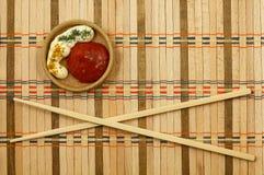 Chopsticks. On a wicker mat Stock Images