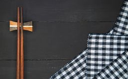 Chopsticks. Wooden chopsticks over plaid tartan tablecloth on black wooden table in top view Stock Image