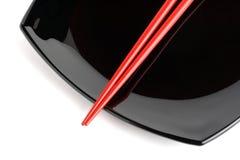 Chopstics rosso su un piatto nero Fotografia Stock