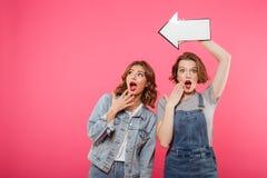 Choqué deux amis de dames tenant la flèche Photo libre de droits