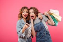 Choqué deux amis de femmes tenant des paniers utilisant le téléphone portable Photographie stock