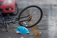 Choque de coche con la bicicleta en el camino, día lluvioso del accidente foto de archivo libre de regalías