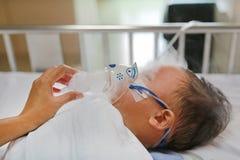 Chora chłopiec i inhalacyjną terapię maską inhalator na cierpliwym łóżku przy szpitalem Oddechowy syncytial wirus RSV zdjęcia stock