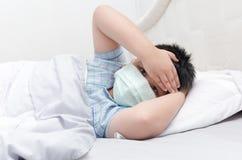 Chora chłopiec z higieniczny maskowym kłama puszek na łóżku obraz royalty free