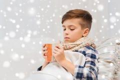 Chora chłopiec pije herbaty w domu z grypą w szaliku Obraz Stock