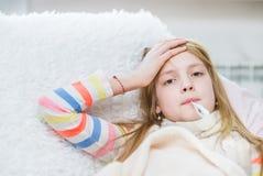 Chora dziewczyna dotyka jej czoło z termometrem w usta zdjęcie royalty free