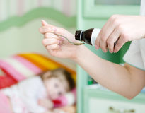 Chora dziewczyna oczekuje jej lekarstwa dolewanie w łyżce w zdjęcia stock