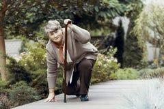 Chora kobieta czekać na poparcie po klatka piersiowa bólu z chodzącym kijem obrazy stock