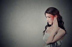Chora kobieta ma uszatego ból dotyka jej bolesną kierowniczą świątynię barwiącą w czerwieni zdjęcie stock