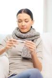 Chora kobieta patrzeje termometr z grypą w domu Obraz Royalty Free
