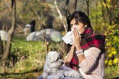Chora kobieta relaksuje w jesień parku z jej psem zdjęcie royalty free