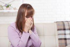 Chora kobieta siedzi w domu z wysoką gorączką Zimno, grypa, febra i migrena, kichnięcie kosmos kopii nos cieknący zdjęcie stock