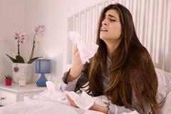 Chora kobieta w łóżkowy mienie chusteczki kichać silny Fotografia Royalty Free