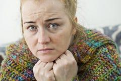 Chora kobieta z migreny obsiadaniem pod koc zdjęcia royalty free