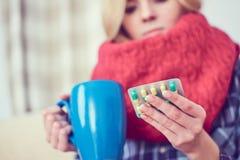Chora młoda dziewczyna z pigułkami i filiżanka herbaciany obsiadanie na kanapie zdjęcie royalty free
