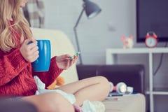 Chora młoda dziewczyna z pigułkami i filiżanka herbaciany obsiadanie na kanapie fotografia royalty free