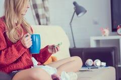 Chora młoda dziewczyna z pigułkami i filiżanka herbaciany obsiadanie na kanapie fotografia stock